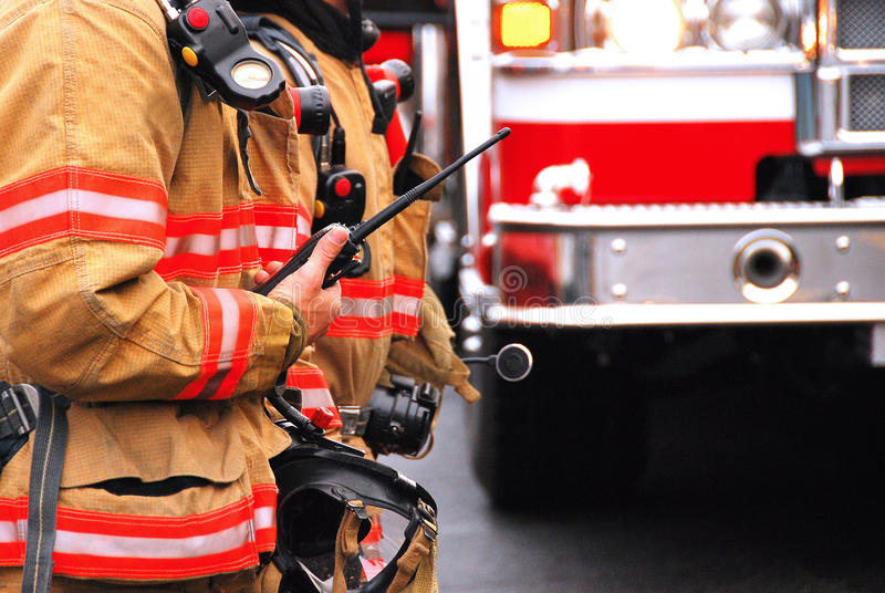 Fire command. Officer at the scene of an emergency with a radio and fire engine in the background stock image