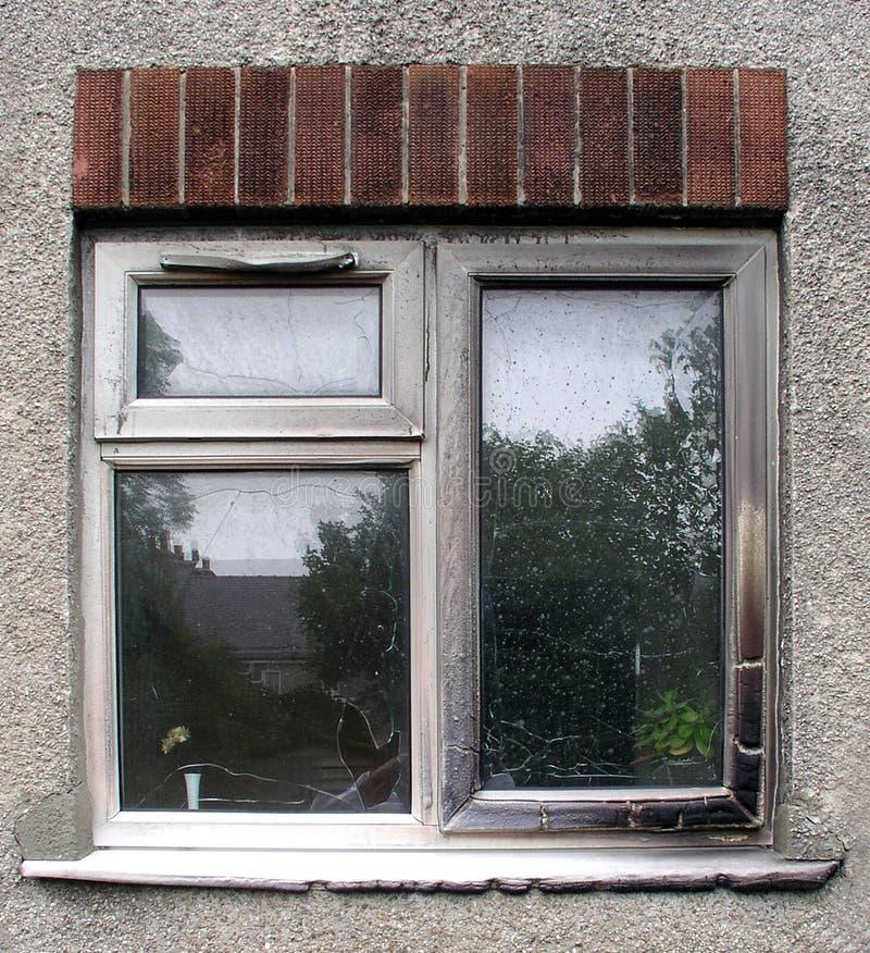 Fire damaged window. PVCu window - showing extensive fire damage royalty free stock photo