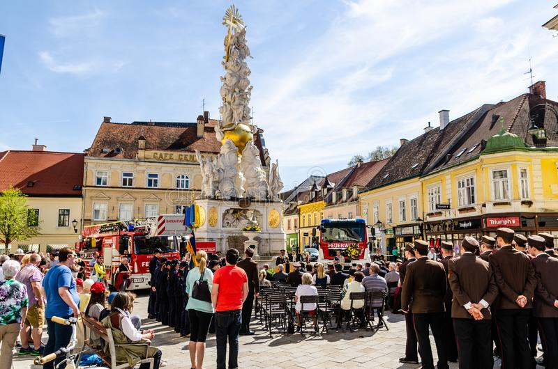 Fire Department and orchestra on city square with gathered people. Baden bei Wien, Vienna - Austria - 25.04.2015: Fire Department and orchestra on city square stock photography