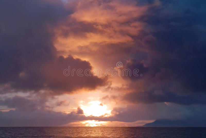 Fire in dramatic sky. Storm. Dark stormy clouds are red colored by sea sunset stock photography