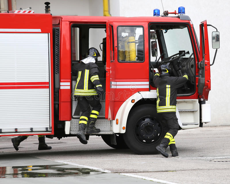 fire engine with many firefighters and equipment for fighting fire stock images