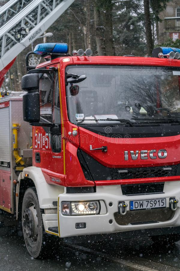Fire engine on the road closeup. Closeup of a fire engine cabin called in to clear the fallen branchech of pine trees after heavy snowfall in winter in Karpacz royalty free stock photo