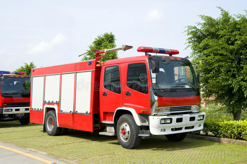 Fire engines in park. Side view of two red fire engines in park with tree in background stock photo