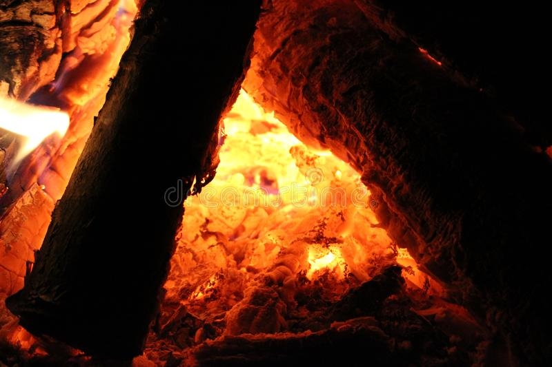 On fire - enter the triangle. Campfire close up between the logs, into the secret world of the inner embers. Might be mid-summer, but better in the fall or stock photo