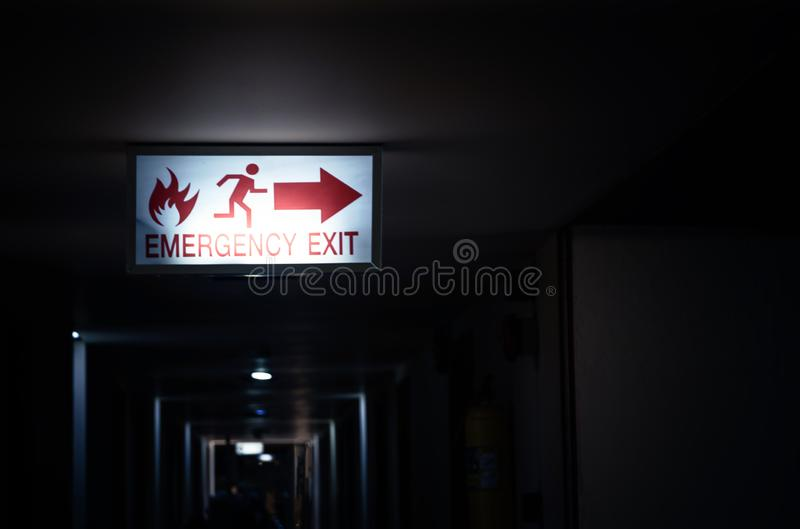 Fire escape label light in hotel at night. Time stock images