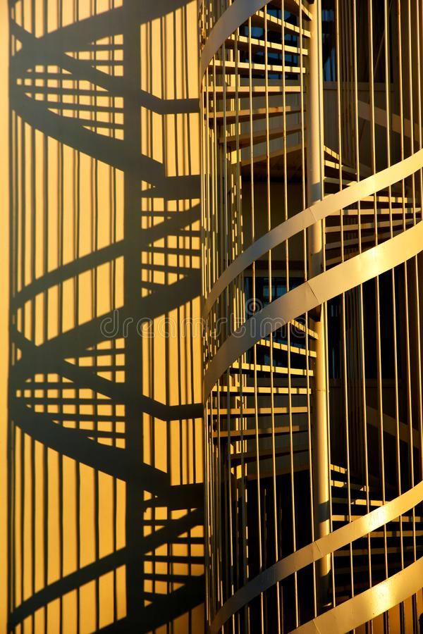 Corkscrew stairs and shadows. Fire escape, spiral staircase and her shadow in warm yellow and golden colors stock image