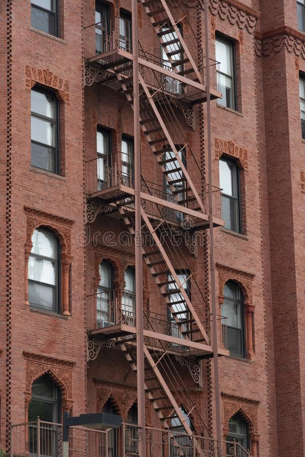 Fire escape stairs-downtown back alley architecture-steel and red brick background. Red Fire escape stairs-downtown back alley architecture-steel and red brick stock photography
