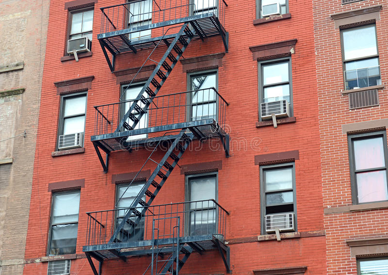 Fire escape stairway on exterior of red brick walkup apartment building. In New York City stock photo
