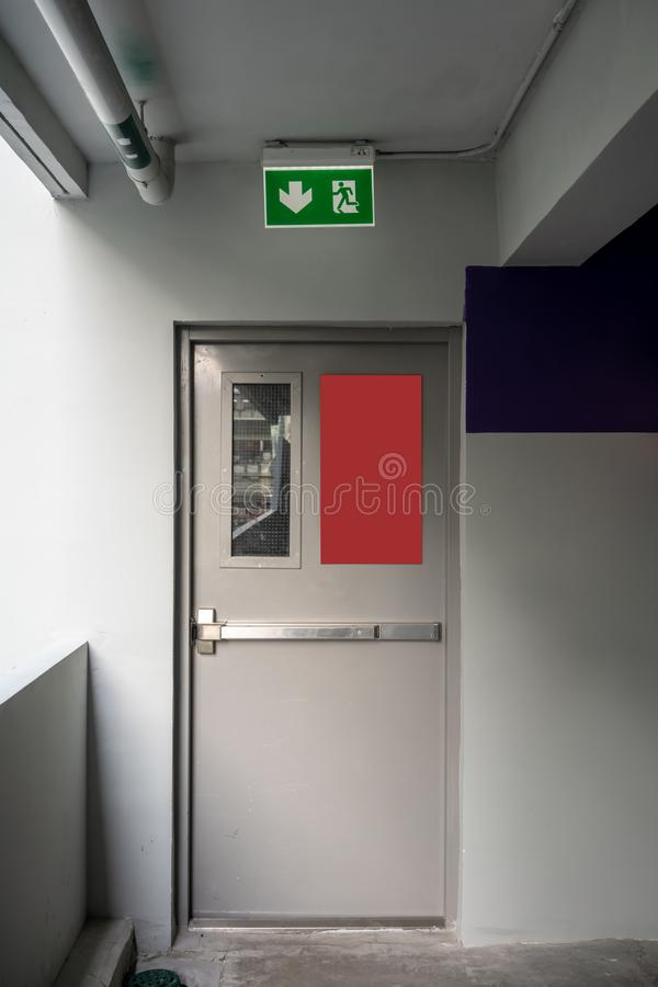 Fire exit emergency door grey color metal material and concrete stock images