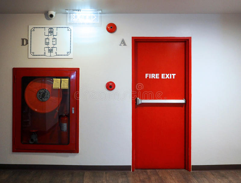 Fire exit emergency door red color metal material. Fire exit emergency door red color metal material with alarm for safety protection and wood floor and white royalty free stock images