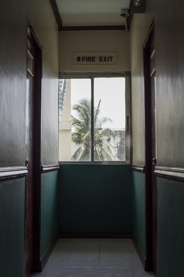 Fire exit in a hotel corridor with a coconut tree outside the window.  royalty free stock images