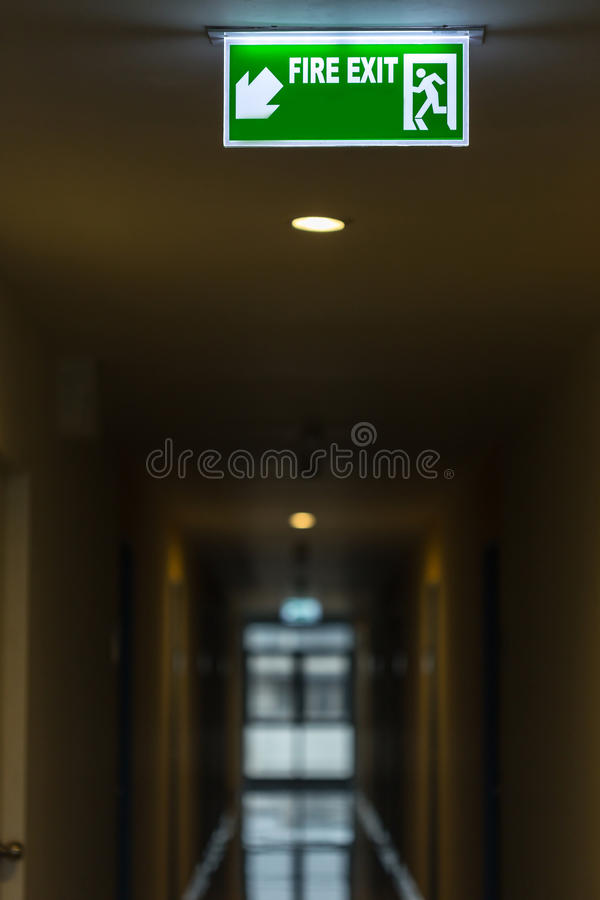 Fire exit sign in hotel corridor. Green fire exit sign in hotel corridor royalty free stock photo