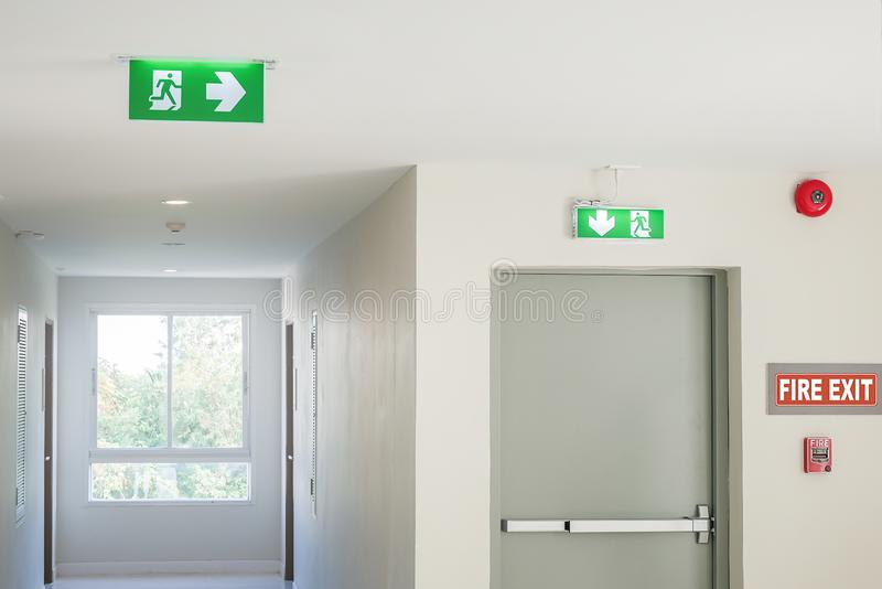 Fire exit sign with light on the path way in the hotel or office.  royalty free stock photos