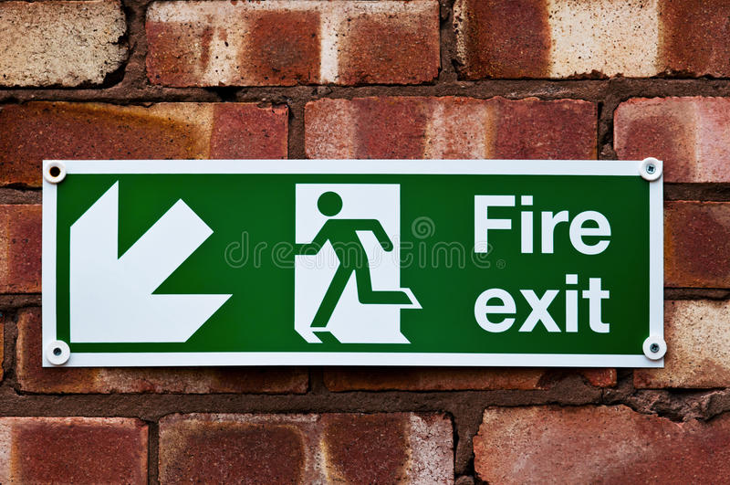 Fire exit sign on the red clay brick wall royalty free stock photo