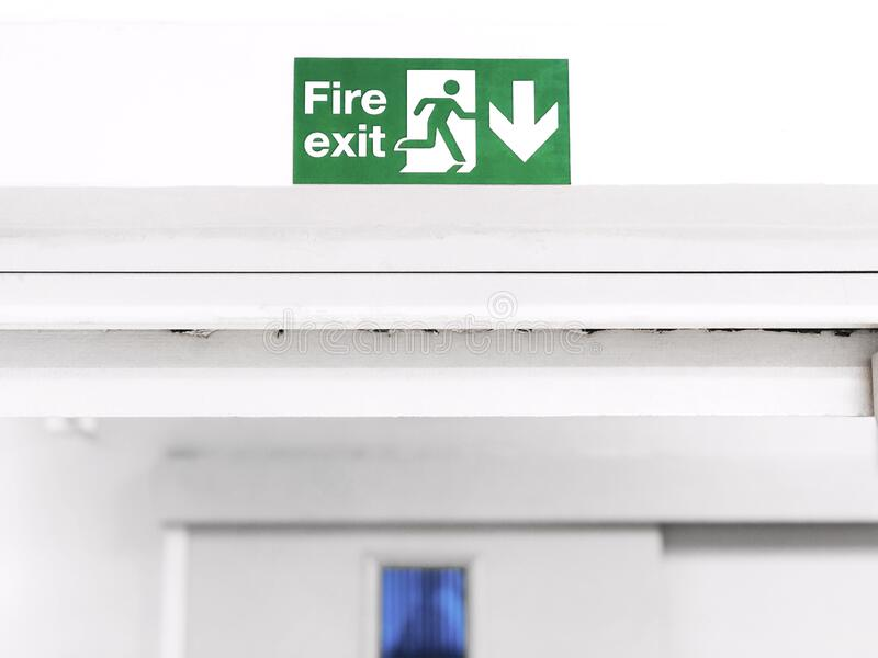Fire Exit sign on the wall entry the room, green safety symbol icon isolated in the white door. Caution for warning in dangerous. Fire Exit sign on the wall royalty free stock photos