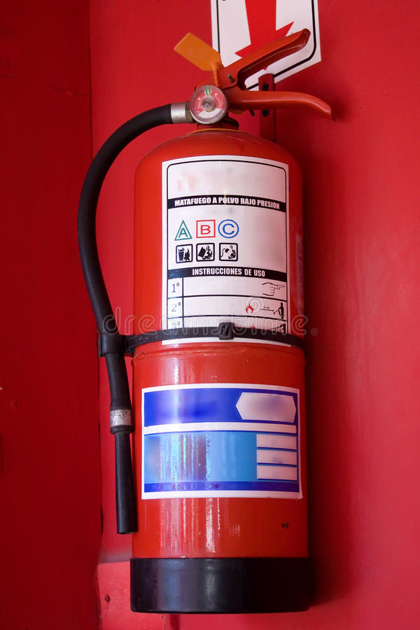 Fire extinguisher. In red wall royalty free stock photo
