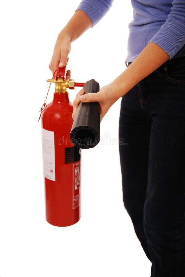 Fire extinguisher. Lady holding fire extinguisher over white stock image