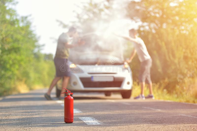 Fire extinguisher against car incident on the road with smoke on. The engine royalty free stock images