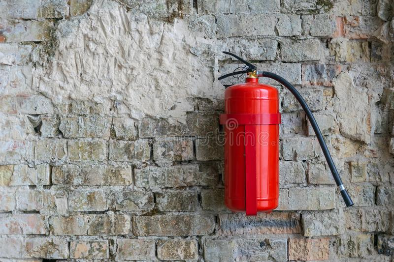 Fire extinguisher on a brick wall construction building location stock image