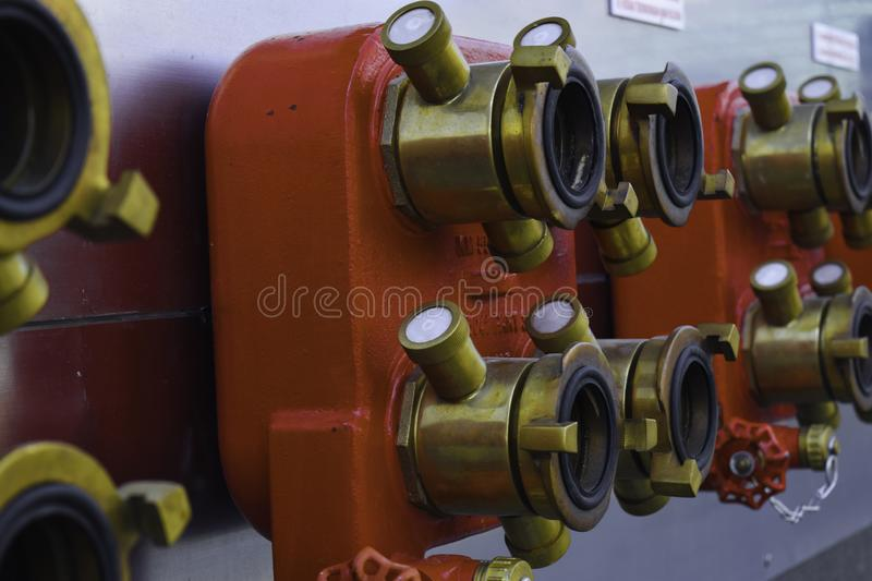 Fire extinguisher connection to the station sprinkler system on the wall background stock image