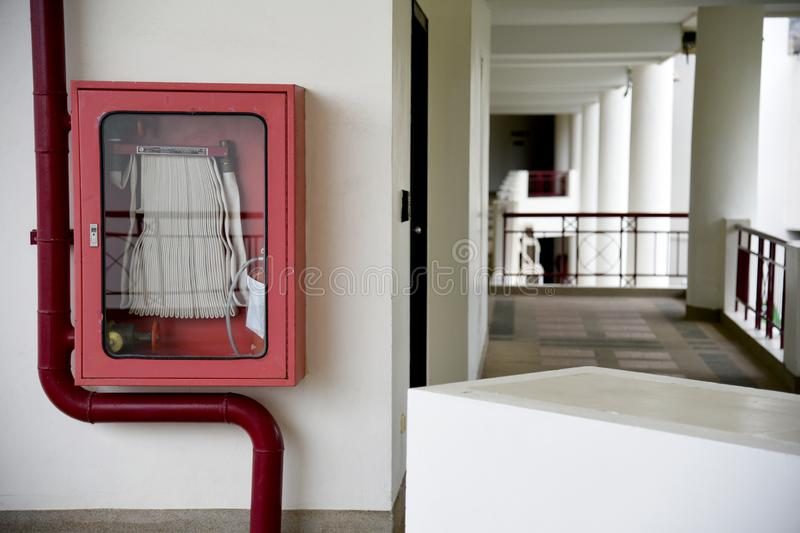 Fire extinguisher and fire hose reel in hotel corridor. Fire hoses rack for use. Fire extinguisher and fire hose reel in hotel corridor. Fire hoses rack for use stock photography