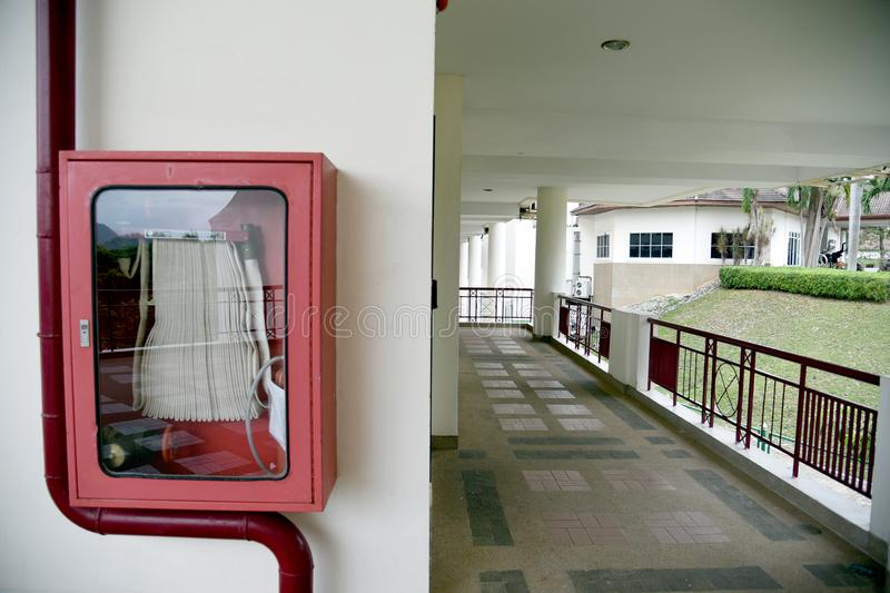 Fire extinguisher and fire hose reel in hotel corridor. Fire hoses rack for use. Fire extinguisher and fire hose reel in hotel corridor. Fire hoses rack for use stock photo