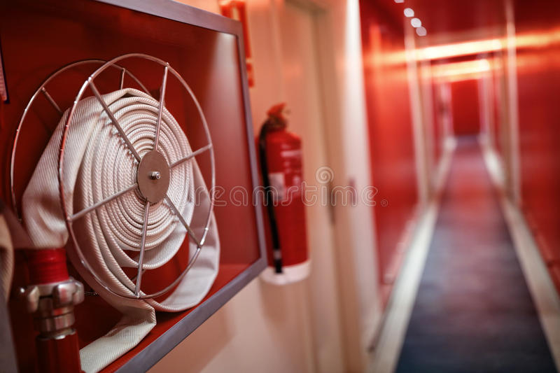 Fire extinguisher and hose reel in hotel corridor. Fire extinguisher and fire hose reel in hotel corridor royalty free stock photos