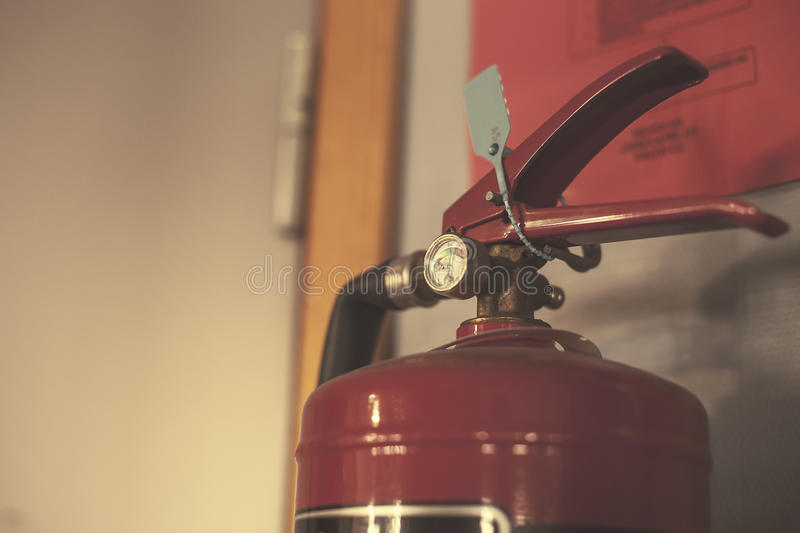 Fire extinguisher with pressure odometer in the gray room royalty free stock photos