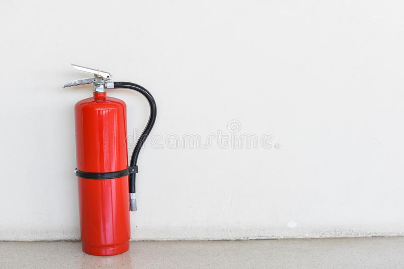Fire extinguisher tank on the background wall royalty free stock photography
