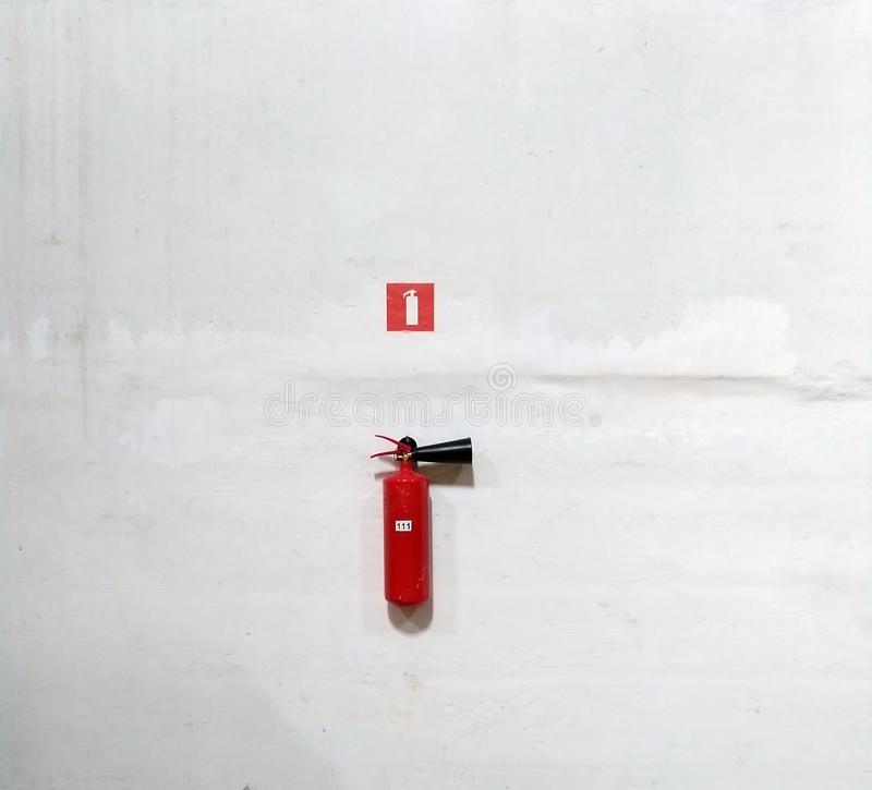 Fire extinguisher on white wall, ready for use. Close-up, background, icon, water, house, office, safety, sign, chemical, danger, emergency, equipment royalty free stock images