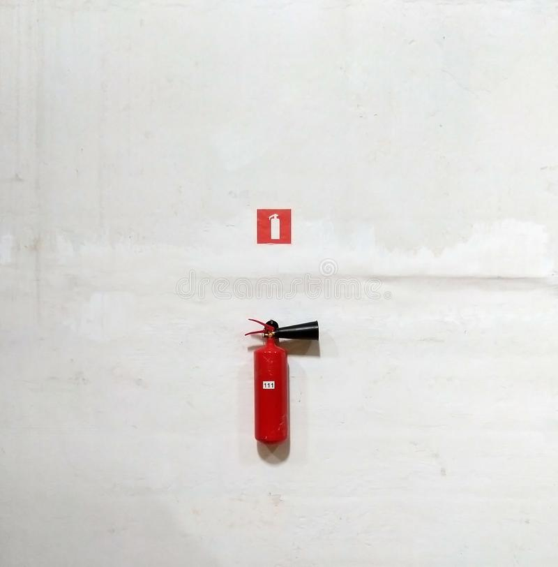 Fire extinguisher on white wall, ready for use. Close-up, background, icon, water, house, office, safety, sign, chemical, danger, emergency, equipment stock photos