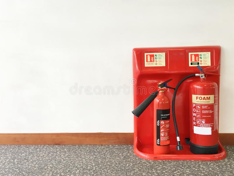 Fire extinguisher in workplace office against plain neutral background. Uk stock photo