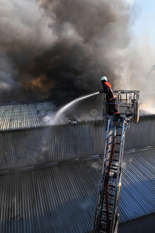 Fire fighter. On a ladder truck in heavy smoke stock photo