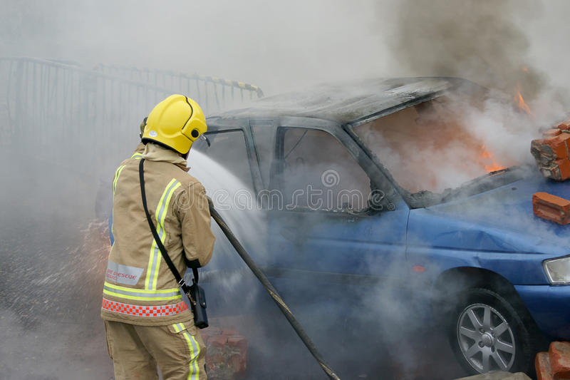 Fire fighter fighting car fire. Crashed into wall royalty free stock images