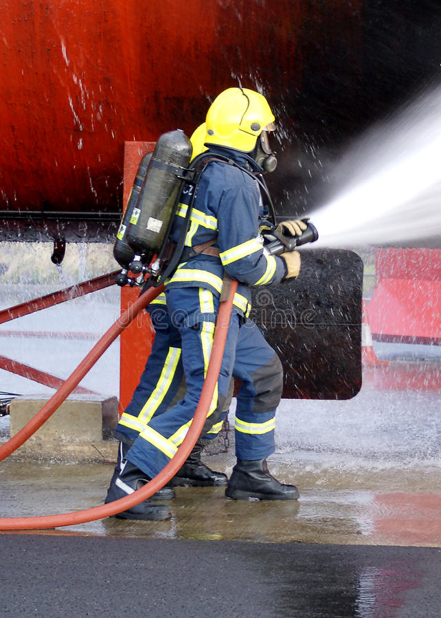 Fire fighter fighting fire with hose. Fire-fighter fighting fire with hose in full BA royalty free stock photography