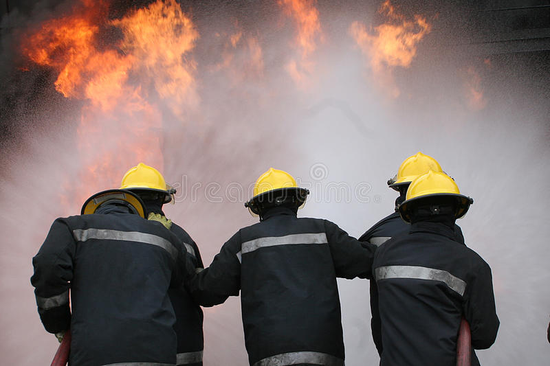 Fire fighter at fire. Fire fighter fighting fire at large incident royalty free stock images