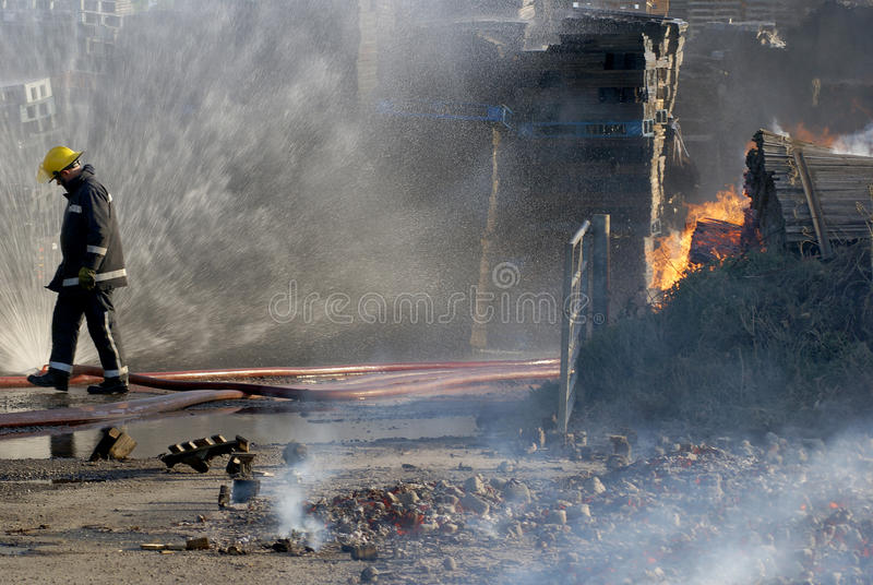 Fire fighter at fire. Fire fighter fighting fire at large incident royalty free stock photography