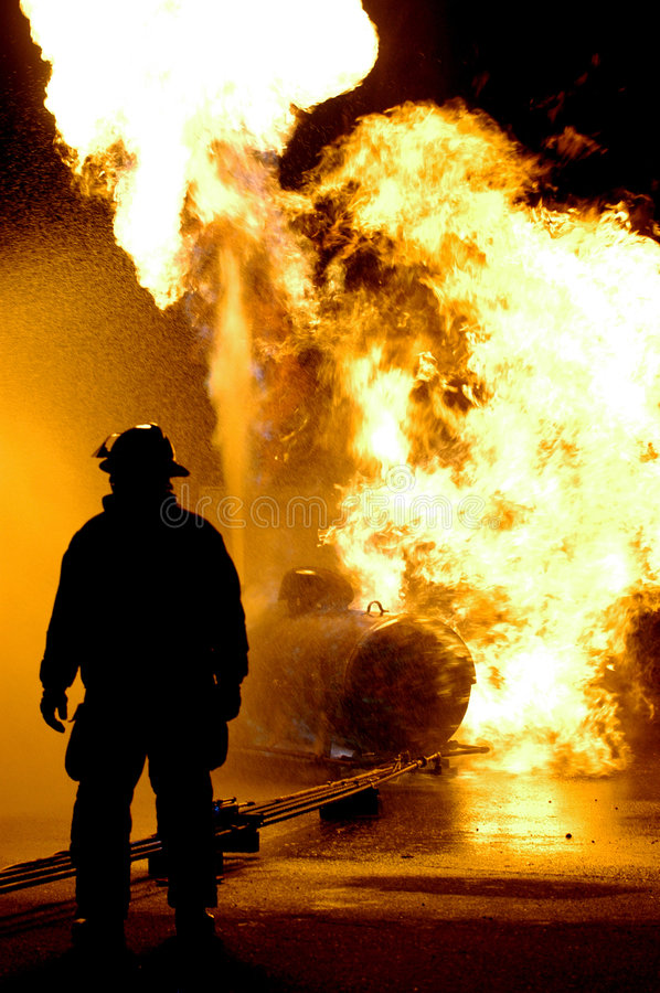 Fire Fighter and Flames. A fire fighter looks on as a propane tank burns. This image was taken during a training seminar for the Fire Academy. NOTE there is royalty free stock images