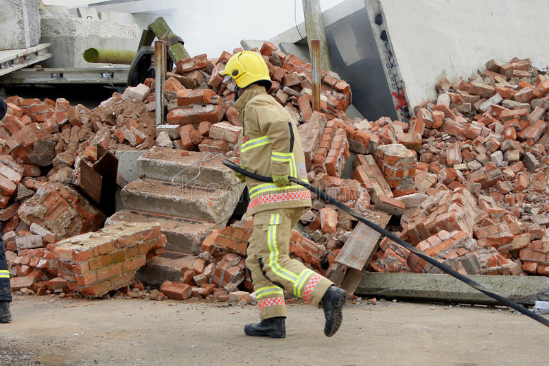 Fire fighter with hose. At building collapse stock photos
