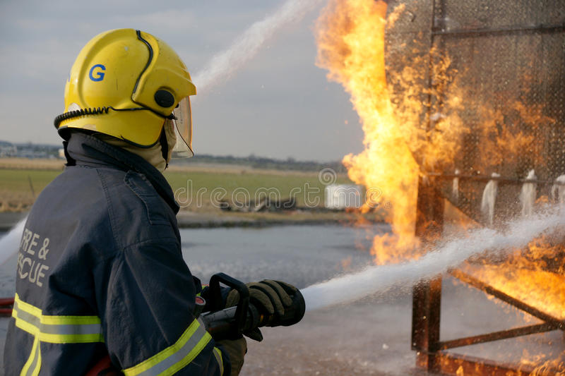 Fire fighter with hose. Fire fighter fighting fire with hose stock photos