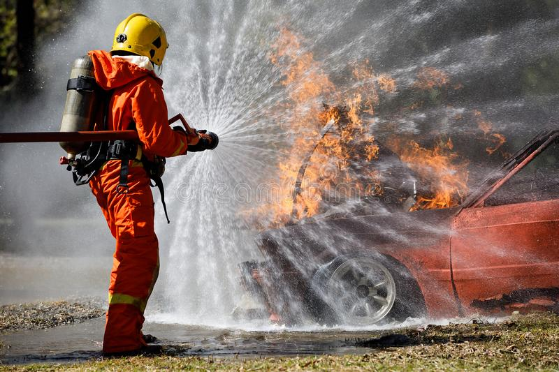 Fire fighter hosing water to extinguish a fire over the car in accident stock image