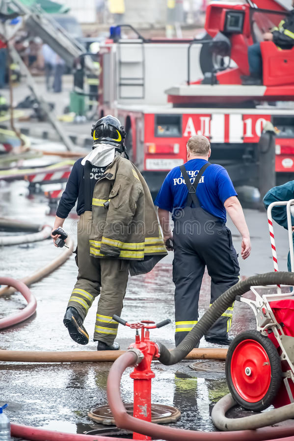 Fire fighter and rescuer walking away building in the drops of water after putting out the stock image