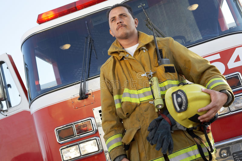 Fire Fighter Standing In Front Of Fire Engine stock photos