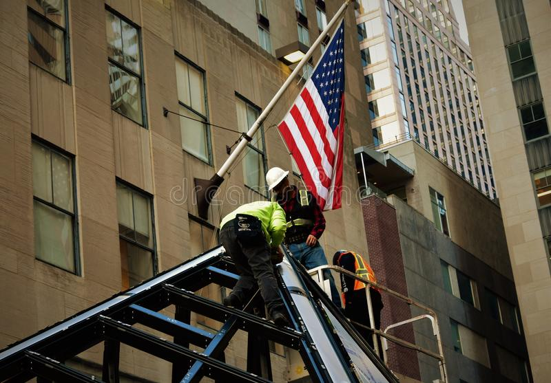 Fire fighters construction in New York City with American flag stock photography