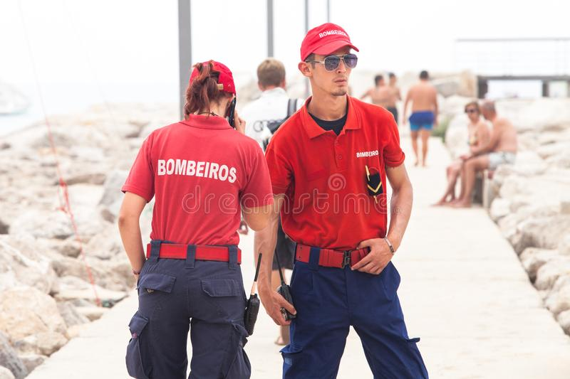 Fire Fighters couple in Portugal. Sesimbra beach stock images