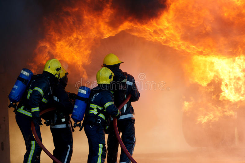 Fire fighters fighting large fire royalty free stock images