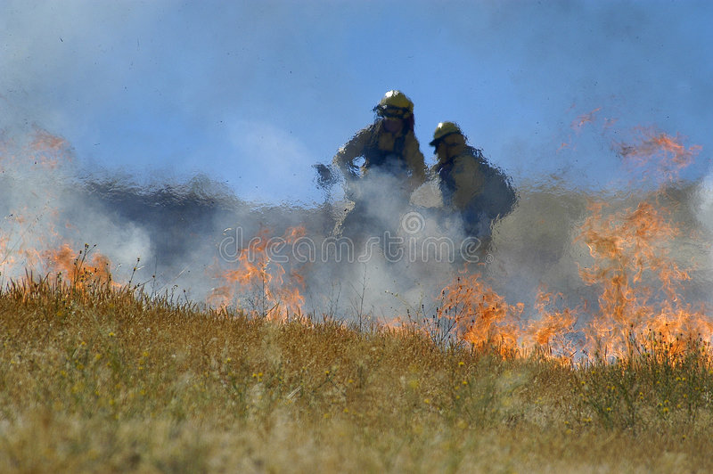 Fire fighters and flames stock photography
