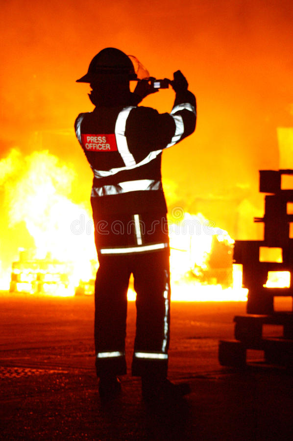 Fire fighters at incident. Fire fighter taking photograph of large fire stock photos