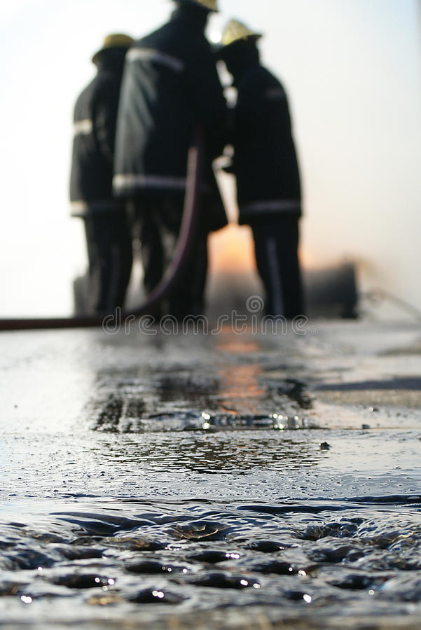 Fire fighters at incident with hose pipe. Water running down the drain at fire incident royalty free stock images