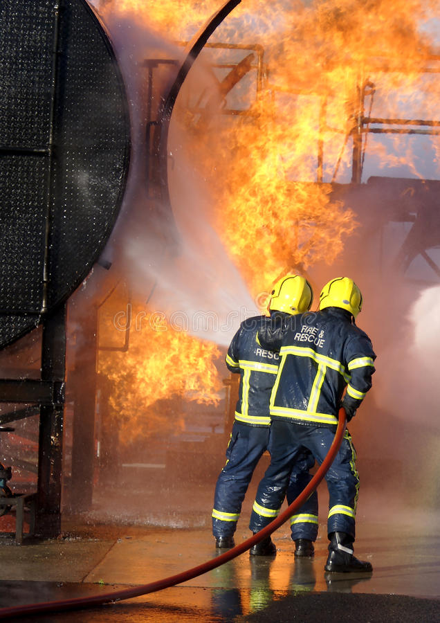 Fire-fighters at large fire. Fire fighters fighting large fire with hose stock photo